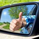 A person sticking their thumb up in the rear-view mirror