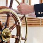 A hand on a ship's steering wheel