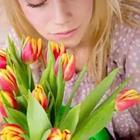 A woman with her face to a bunch of flowers