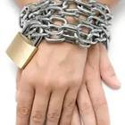 A person's hands tied by chains and a gold lock