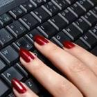 A person's fingers with red painted nails on a black keyboard