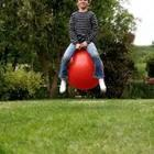 A child sitting on a red ball