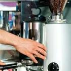 A person's hand touching a grey machine, cofe