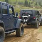 Two black jeeps on a dirt road