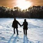 Two people walking and holding hands in the snow