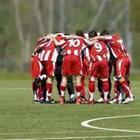 A group of soccer players in a huddle