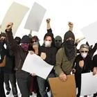 A group of people in masks holding up signs