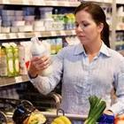 A woman food shopping and holding something up