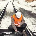 A man in an orange vest and white helmet fixing a railroad track