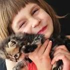 A girl holding a cat to her face and smiling