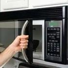 A person with their hand on a microwave door handle