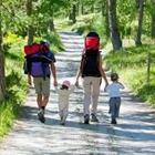 A family walking on a path with the adults carrying backpacks