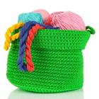 A green basket filled with wool