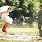 Bride and groom playing in a puddle